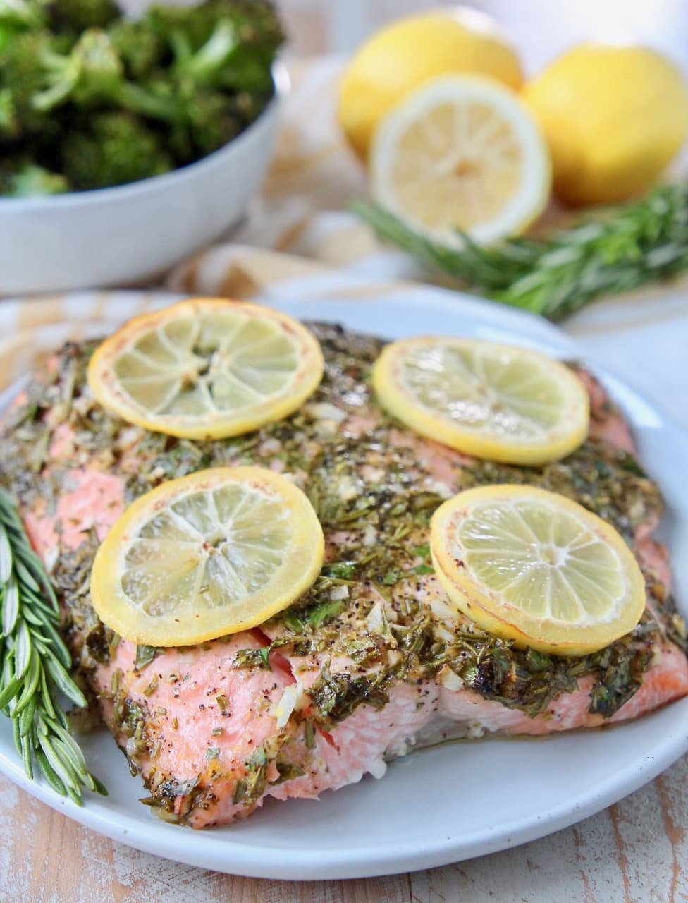 Piece of baked salmon on plate, topped with herbs and lemon slices