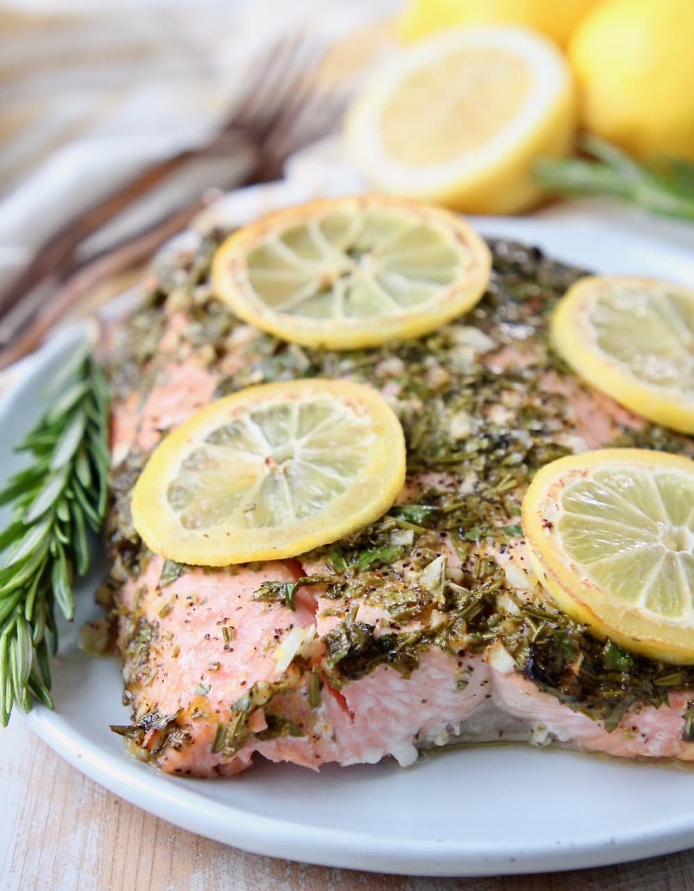 Herb roasted salmon on plate with lemon slices and a rosemary sprig on the side
