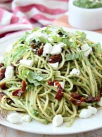 Pesto spaghetti on plate with goat cheese crumbles on top and gold fork on the side