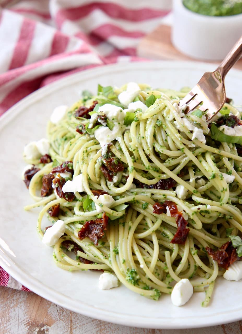 Pesto spaghetti with sun dried tomatoes on white plate with a gold fork twirling the spaghetti on the plate