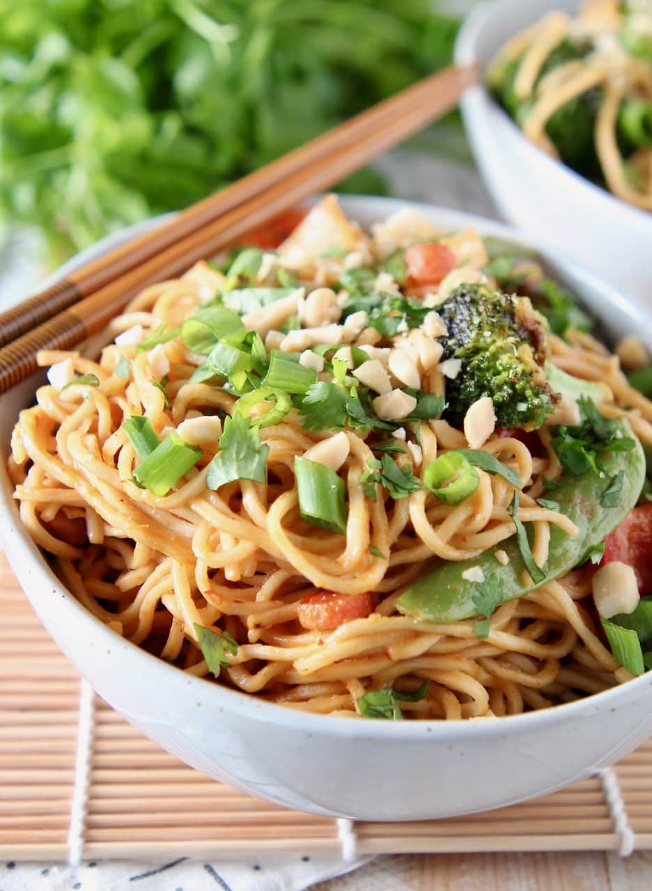 Vegetables and noodles in bowl, topped with green onions and peanuts, with chopsticks on the side of the bowl