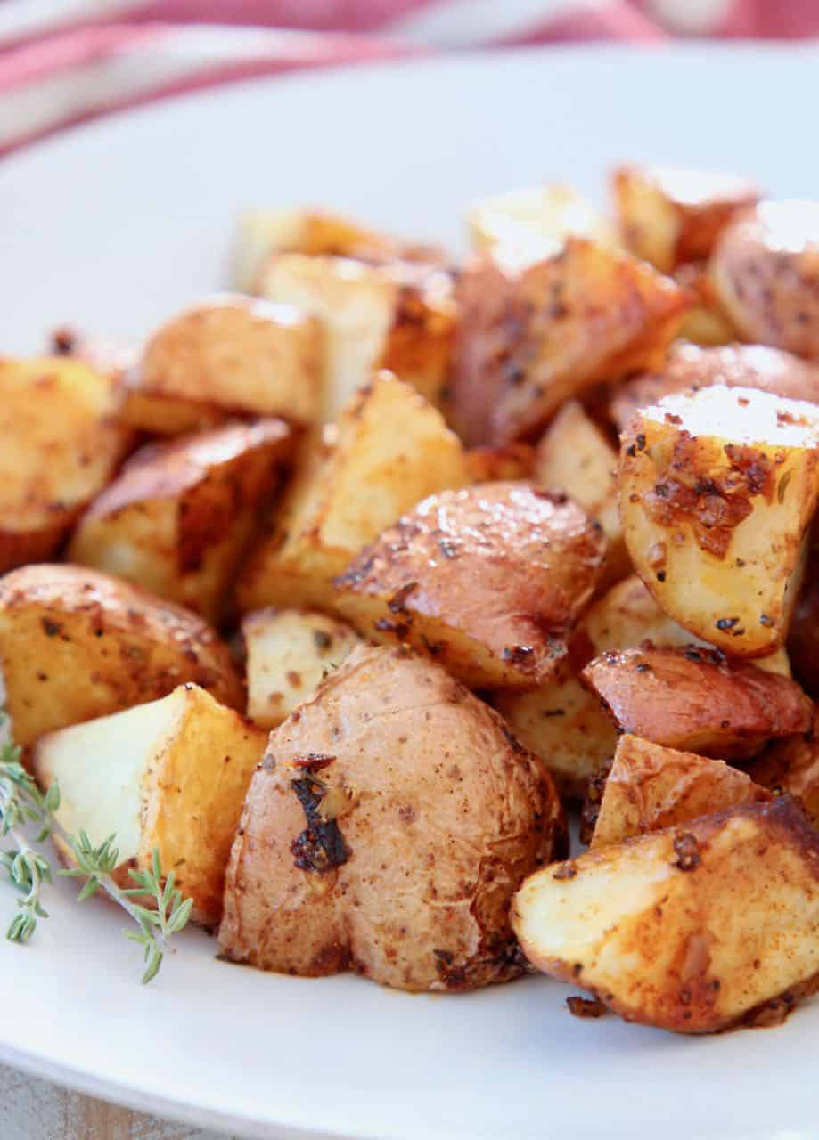Oven roasted cubed Cajun potatoes on white plate