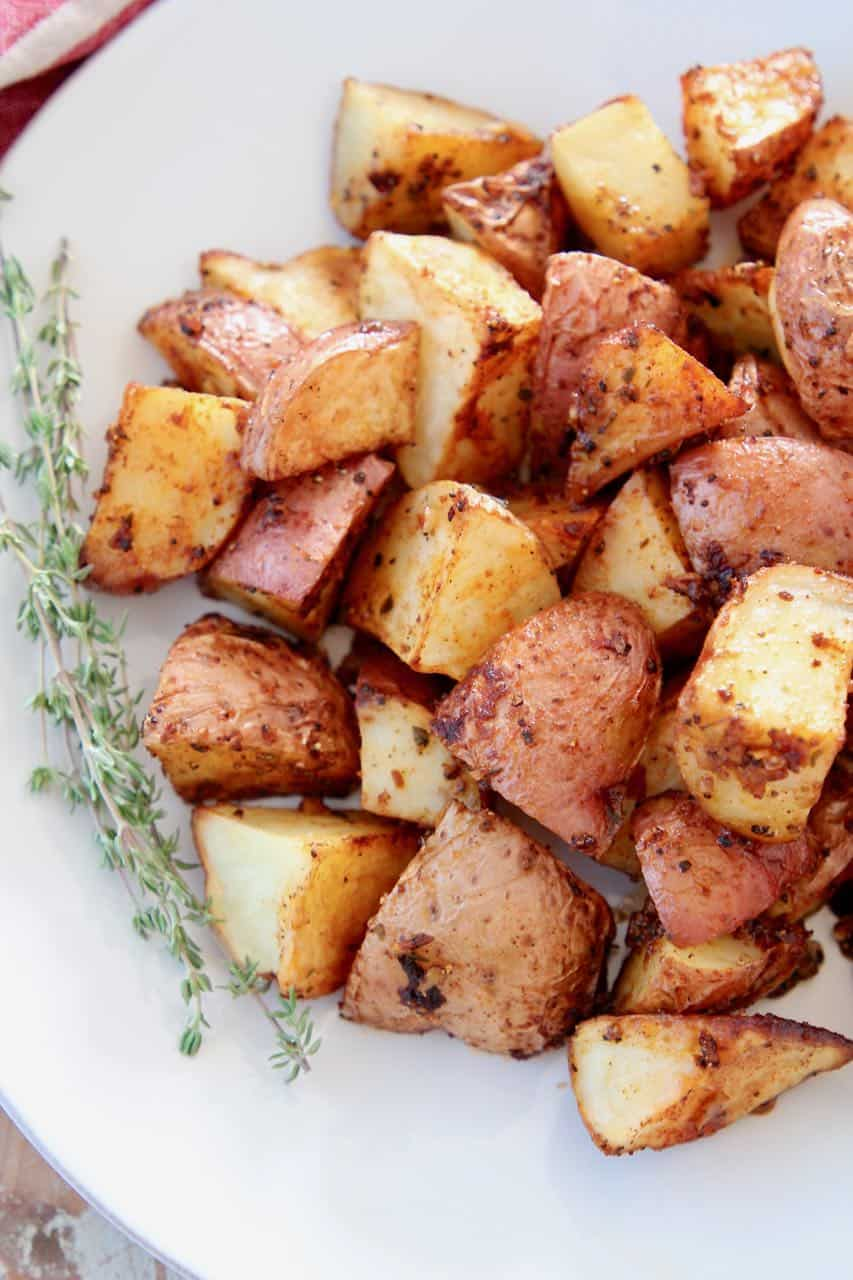 Overhead image of roasted cubed red potatoes on plate with thyme sprigs
