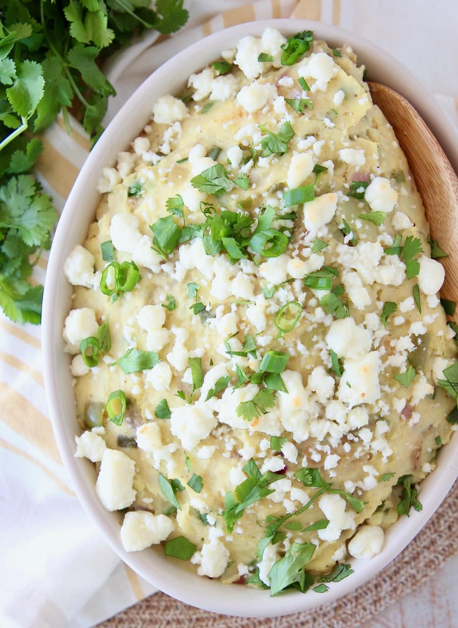 Mashed Mexican Potatoes in a bowl with a wooden spoon, topped with queso fresco and fresh cilantro