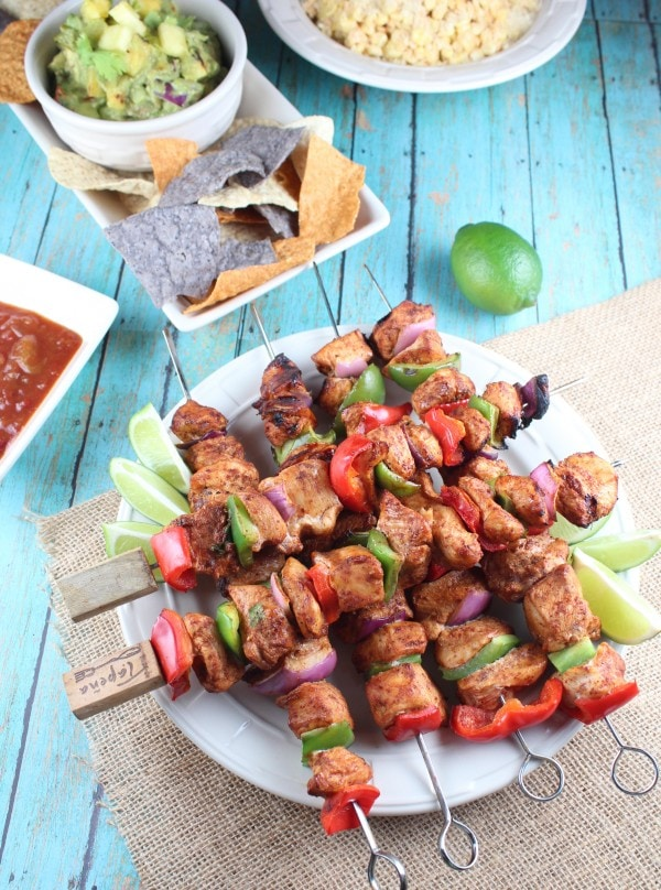 Chicken fajita skewers on plate with lime wedges, with chips and salsa on the side