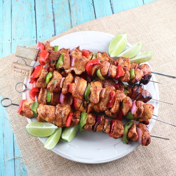 Grilled Chicken Fajita Skewers stacked on top of each other on white plate