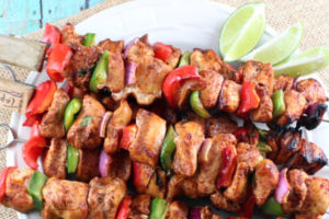 Grilled fajita chicken skewers on plate with lime wedges