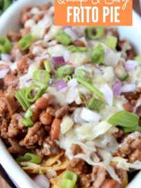 frito chili pie in white oval bowl topped with diced green onions