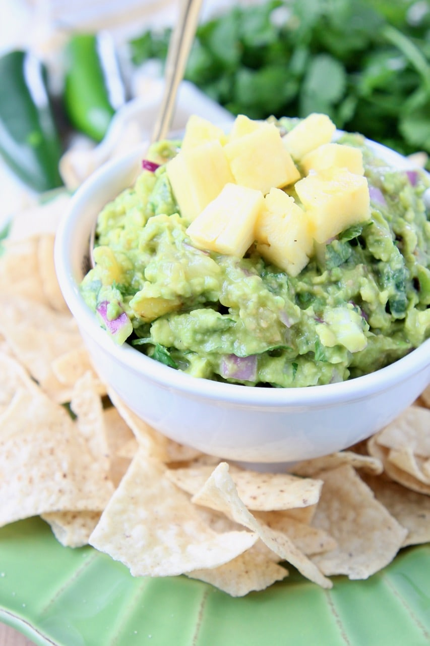 Pineapple guacamole in white bowl, surrounded by tortilla chips