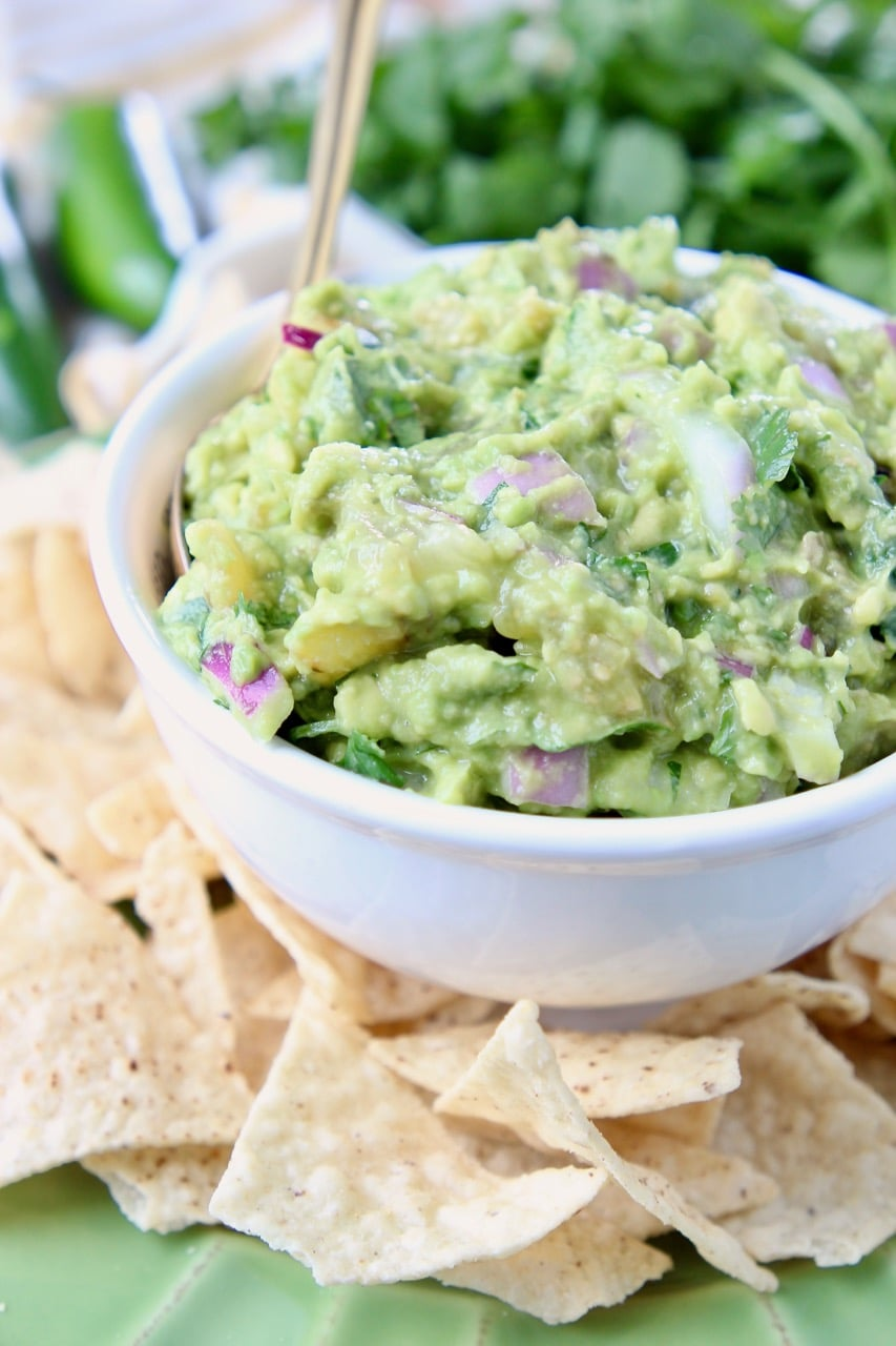Tomatillo guacamole in white bowl, on plate with tortilla chips