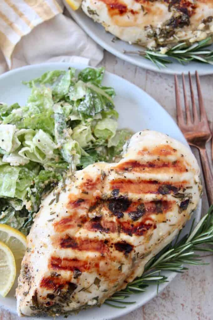 overhead image of grilled chicken breast on plate with salad