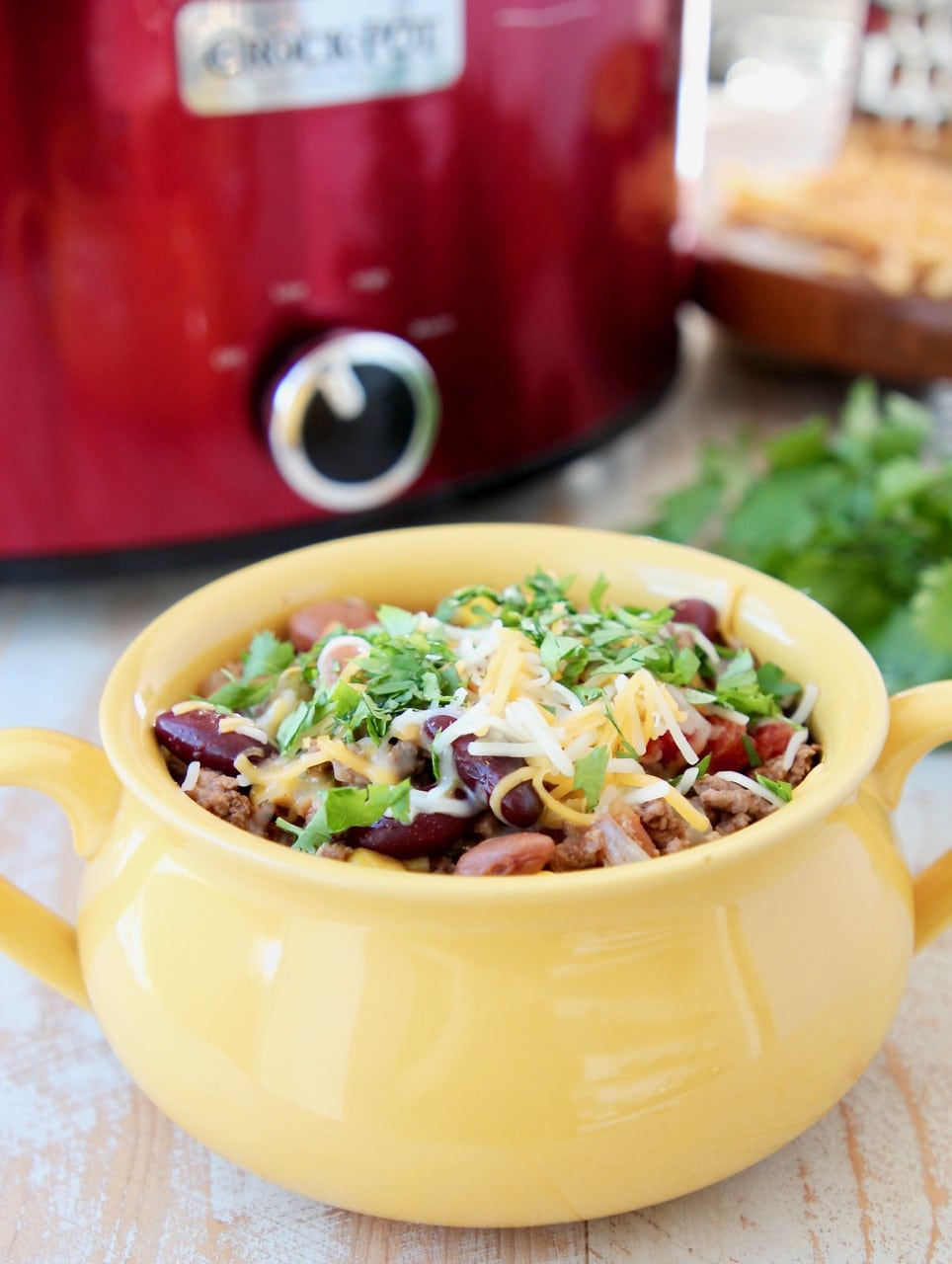 Crockpot taco soup in yellow crock with cheddar cheese and fresh cilantro and red crock pot