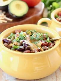 Crockpot Taco Soup in yellow crock with gold spoon, topped with cheddar cheese and fresh cilantro
