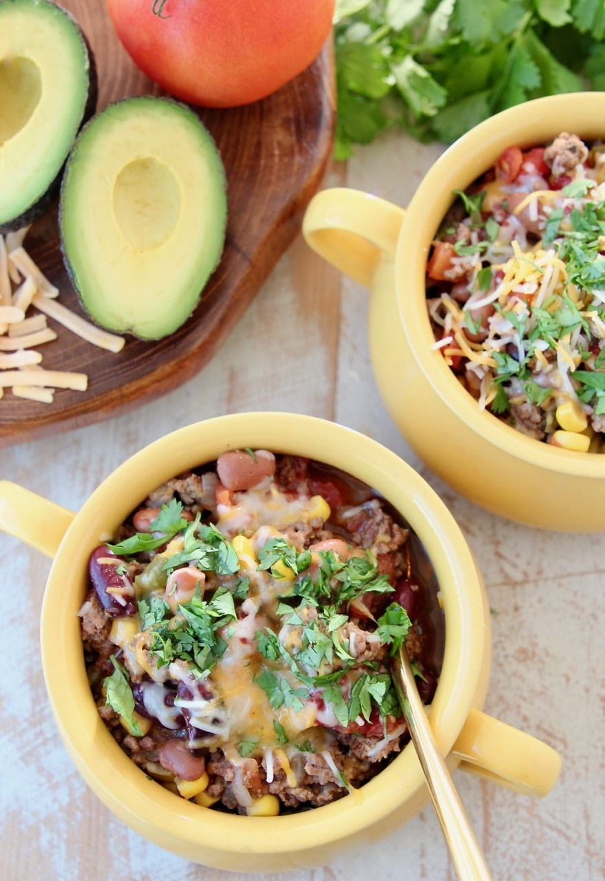 Taco soup in yellow crocks with gold spoon, fresh cilantro, cheddar cheese and fresh avocado