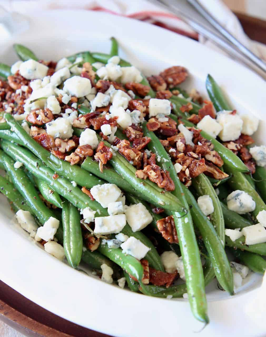 Fresh green beans in serving bowl, topped with pecans and blue cheese crumbles