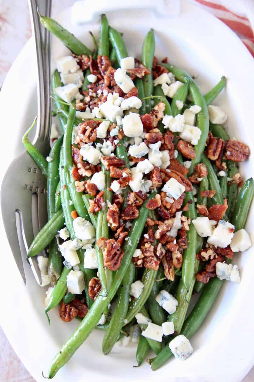 Fresh green beans in bowl topped with bacon crumbles, chopped pecans and blue cheese
