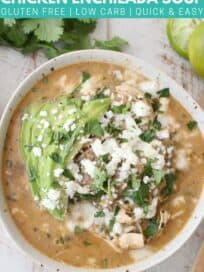 overhead image of chicken enchilada soup in bowl topped with sliced avocado