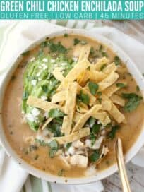 overhead image of chicken enchilada soup in bowl topped with sliced avocado and tortilla strips