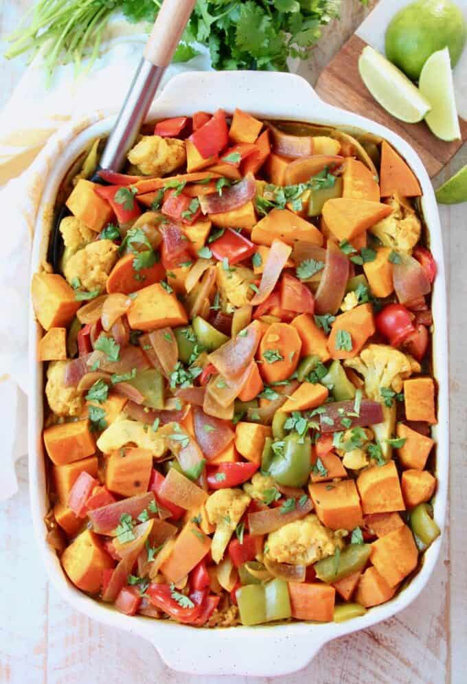Overhead image of vegetable curry casserole in dish with serving spoon