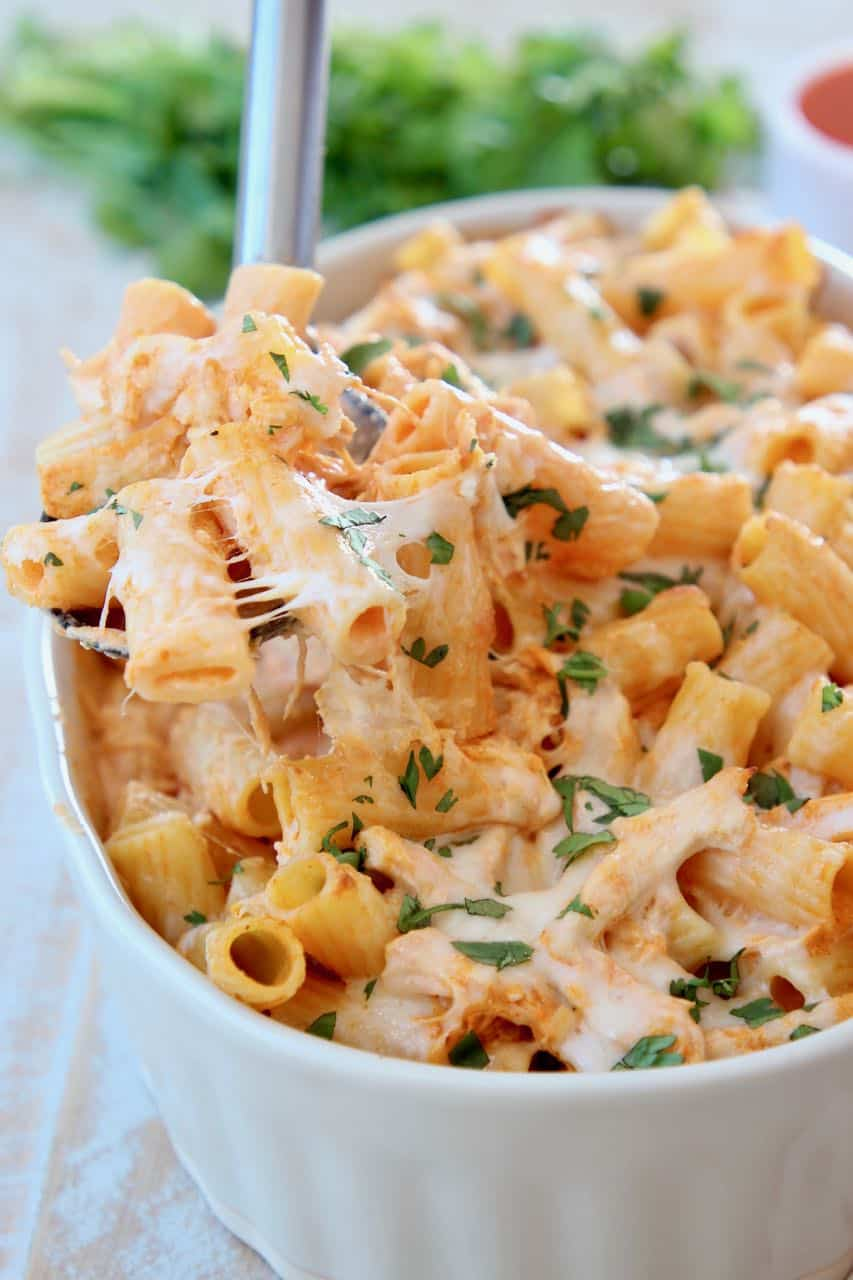 Baked cheesy pasta with spoonful coming out of baking dish