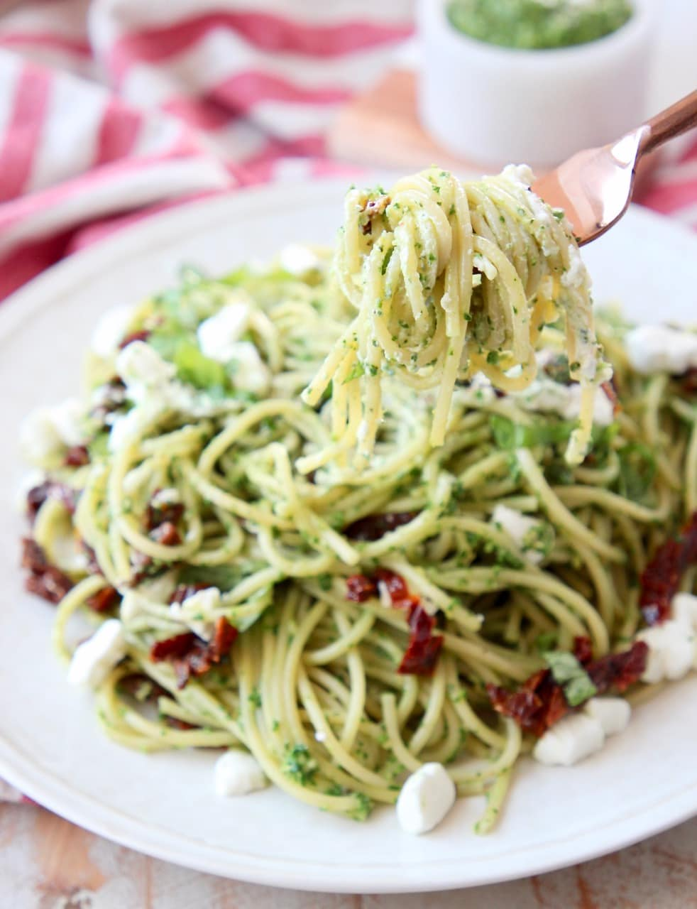 Pesto spaghetti wrapped around a copper fork, held over a plate of pesto spaghetti with crumbled goat cheese and sun dried tomatoes
