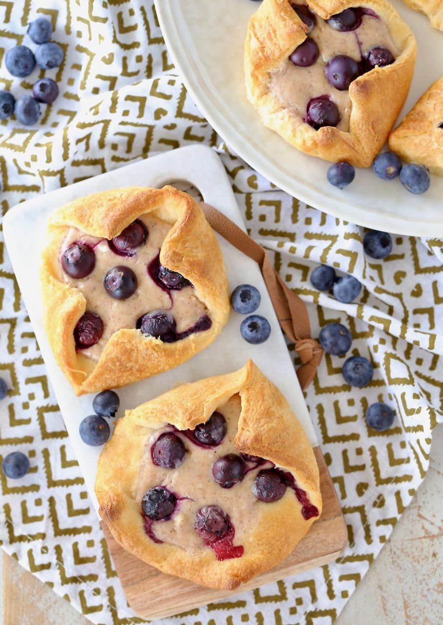 Overhead shot of cream cheese blueberry pastries on cutting board and on round plate with fresh blueberries scattered around the plate
