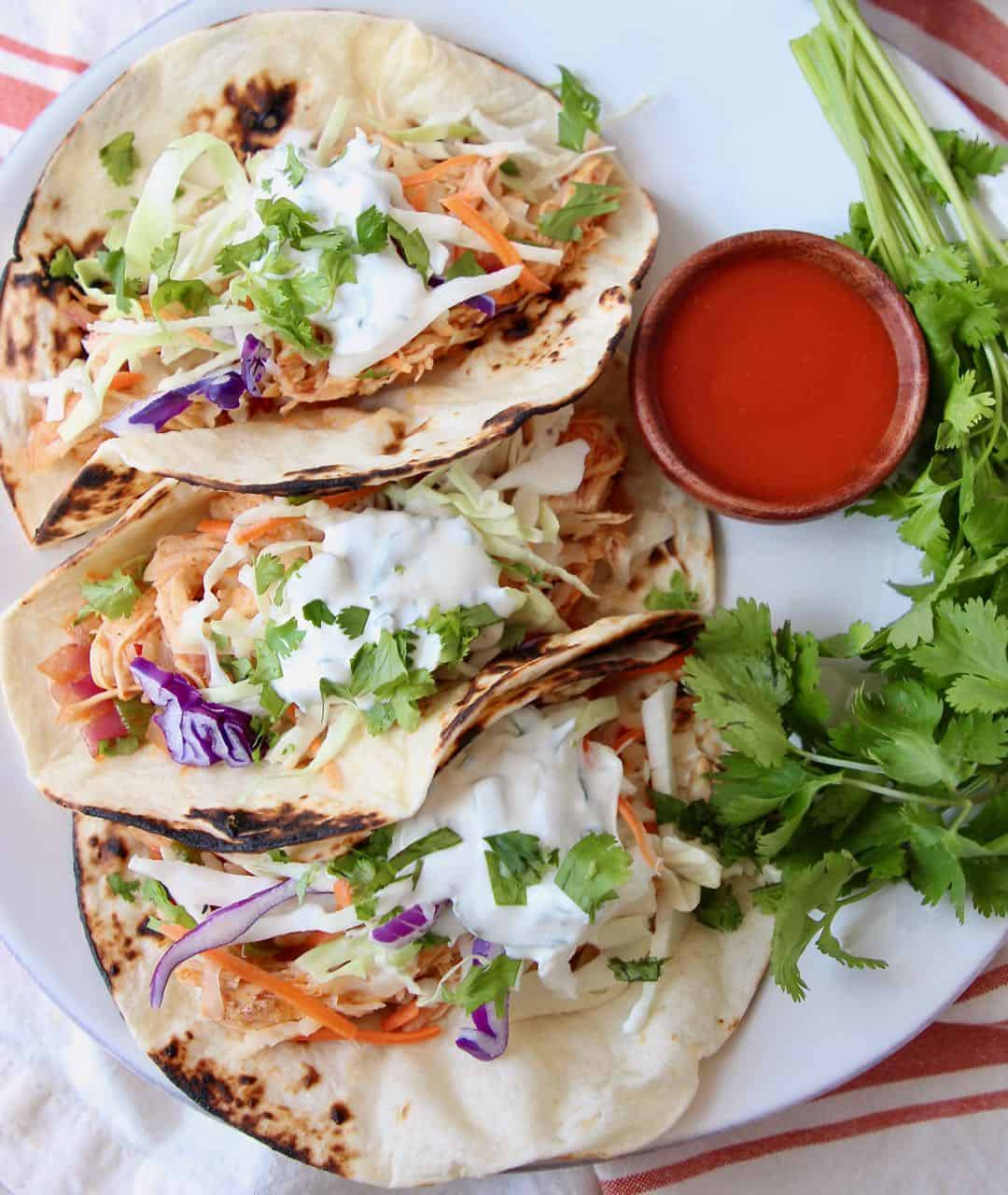 Three buffalo chicken tacos on white plate with side small bowl of buffalo sauce