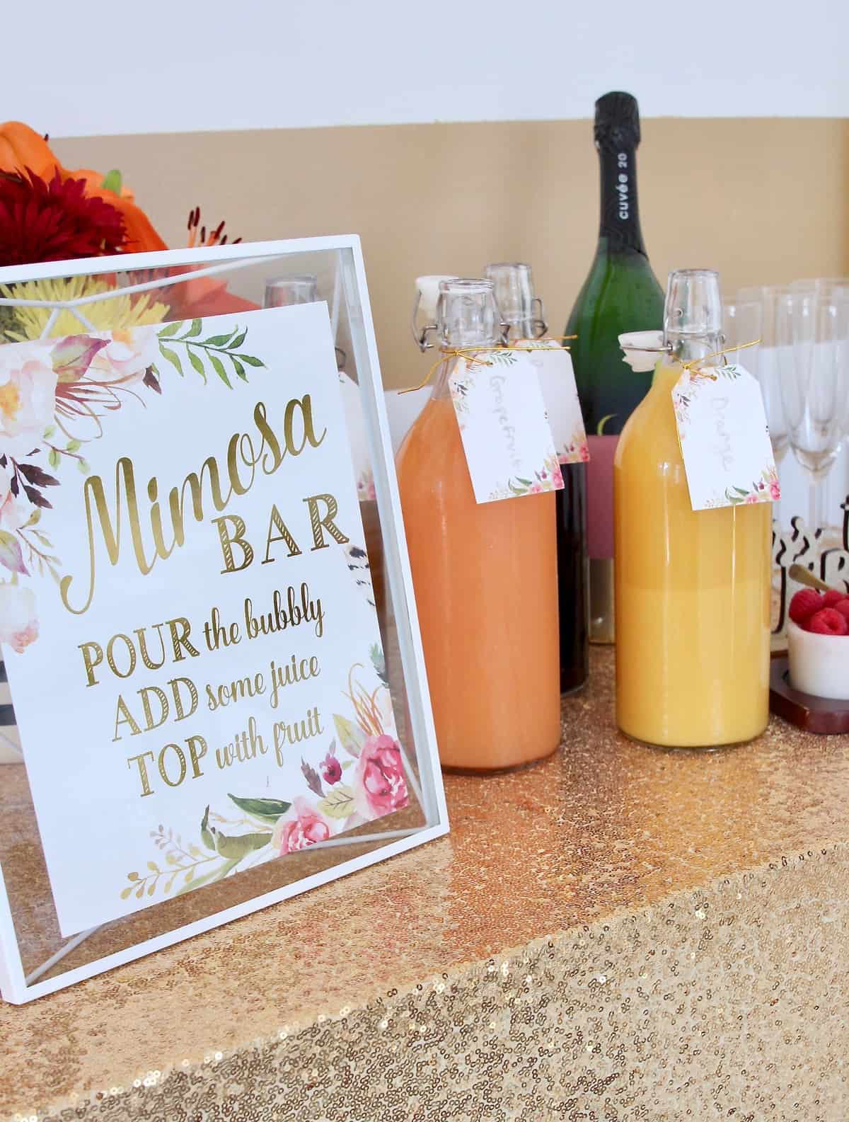 Mimosa bar sign and juices on bar with gold sparkly tablecloth