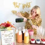 Woman pouring champagne into glass at a mimosa bar