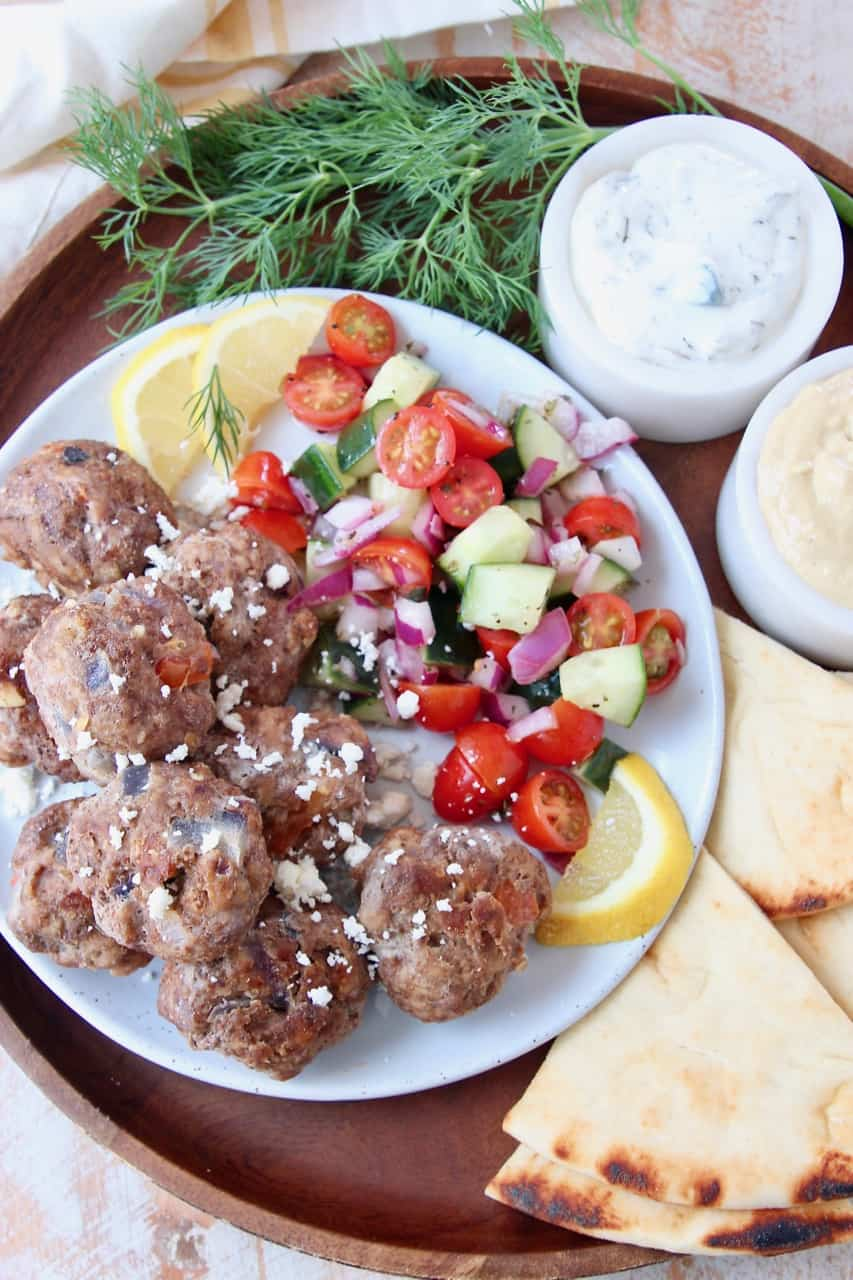 Greek meatballs on plate with tomato cucumber salad and slices of pita bread on the side
