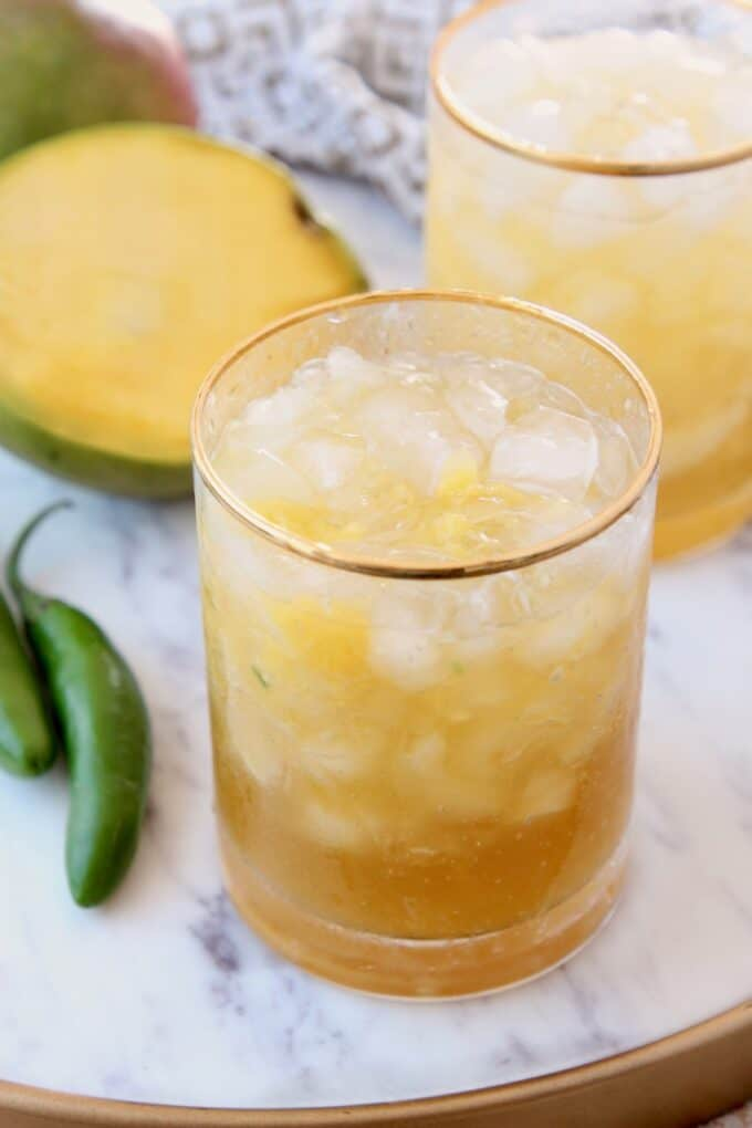 Mango margaritas in glasses on marble tray with fresh mango sliced open