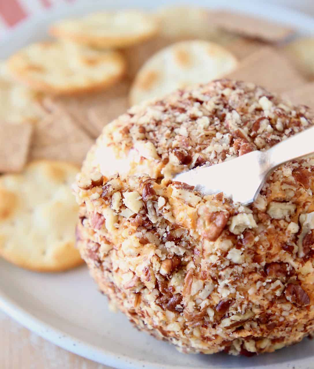 Buffalo cream cheese ball being sliced into with cheese knife