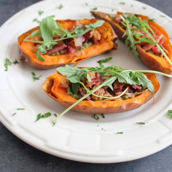 Vitamin packed sweet potatoes are filled with healthy, paleo, sage walnut pesto, crispy bacon and fresh arugula for delicious Paleo Sweet Potato Skins.