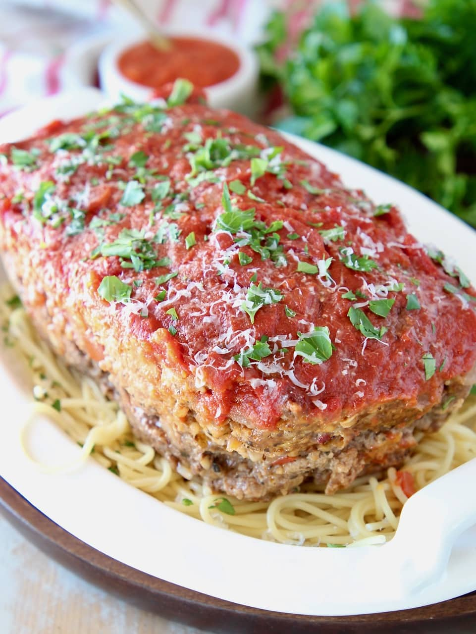 Italian meatloaf sitting on top of a bowl of spaghetti noodles, topped with fresh chopped parsley