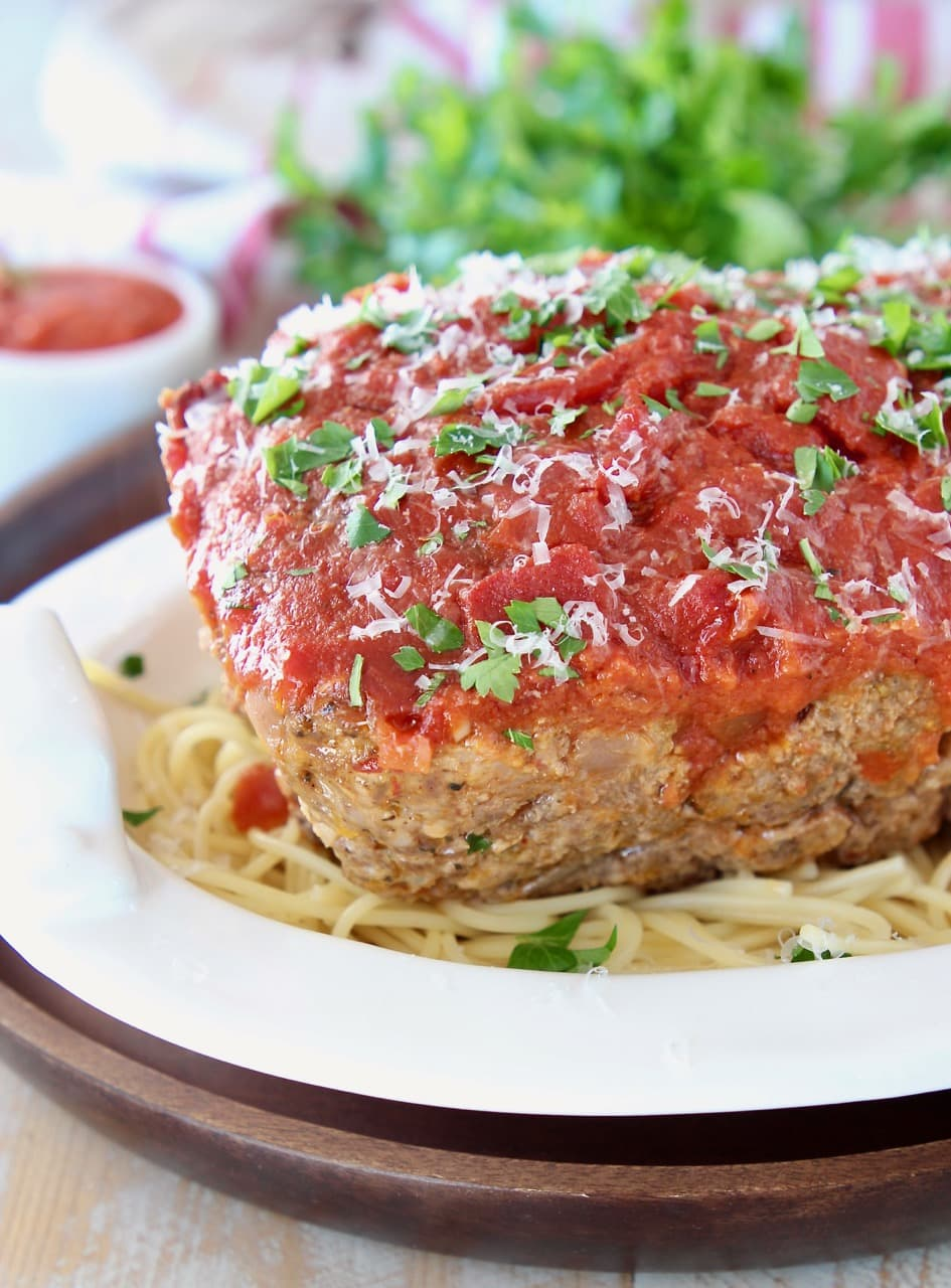 Italian meatloaf covered in marinara sauce on top of spaghetti in a white bowl