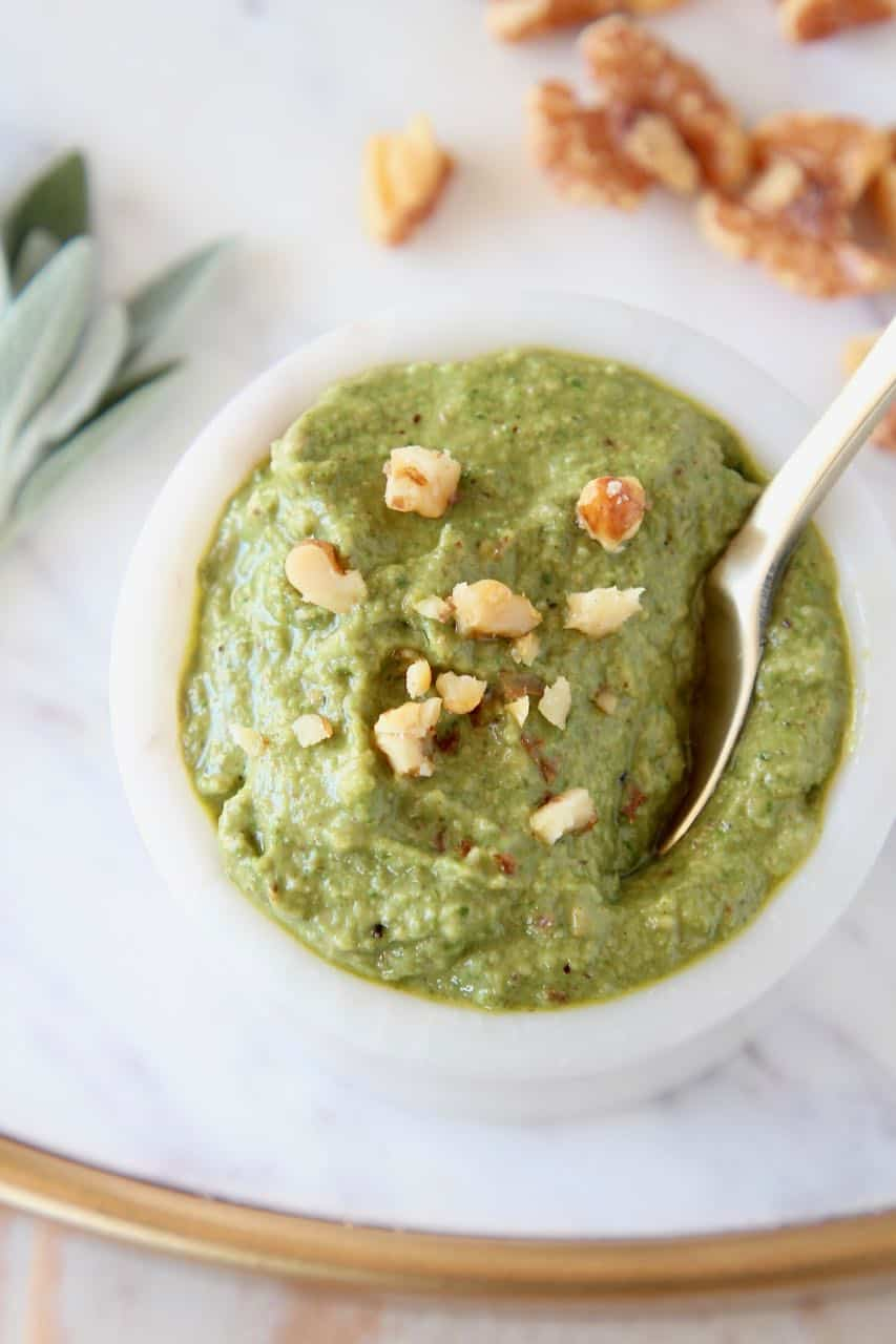 Sage pesto in bowl topped with chopped walnuts