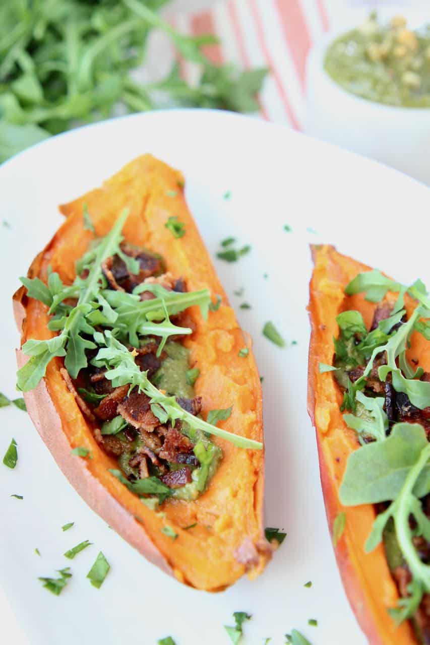 Loaded sweet potato skins with bacon and arugula on white plate