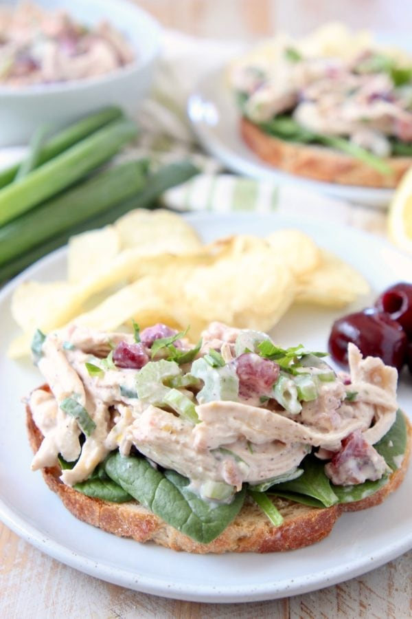 Chicken salad on toast on white plate with potato chips