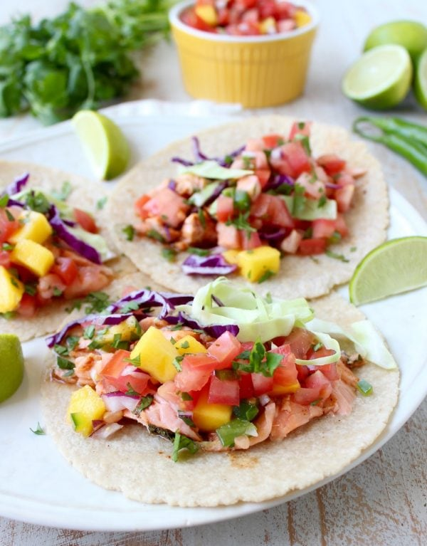 Chipotle honey glazed salmon is placed in warm corn tortillas & topped with fresh mango salsa in this mouth-watering recipe for healthy salmon tacos!