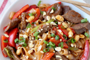 Kung pao beef, noodles and peppers in round white bowl with chopsticks on the side