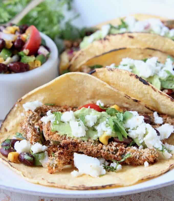 Tacos on plate filled with crispy cactus strips and crumbled queso fresco