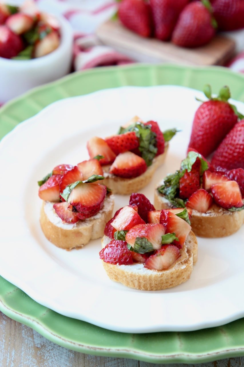 Diced strawberries on top of baguette slices on white plate