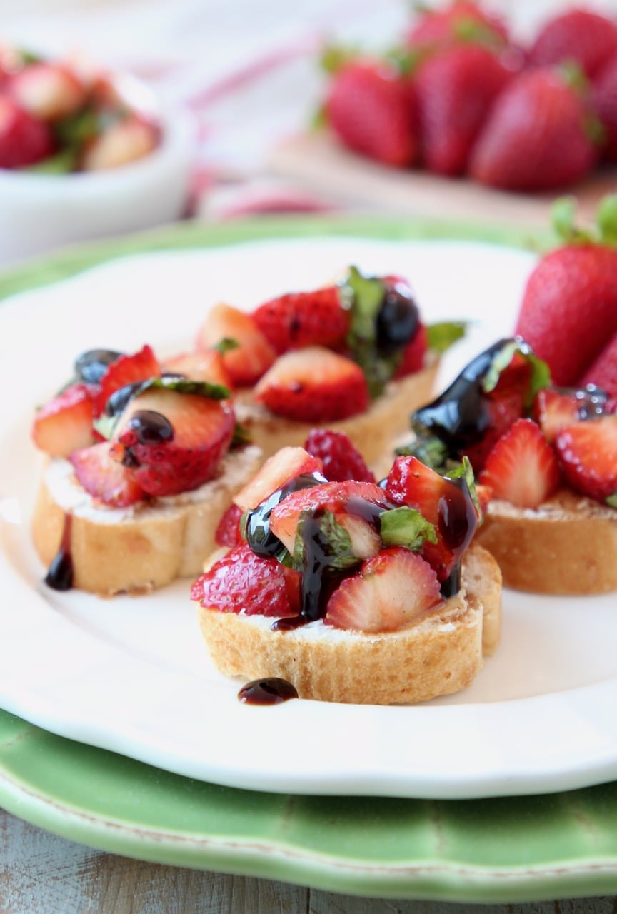 Strawberry bruschetta topped with balsamic glaze on white plate