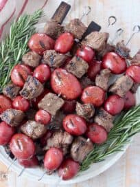 steak and potato kebabs stacked up on plate with rosemary sprigs