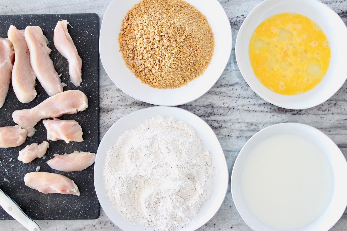 Chicken strip batter station with bowl of eggs, bowl of milk, plate of flour, plate of crushed cereal and raw chicken on cutting board
