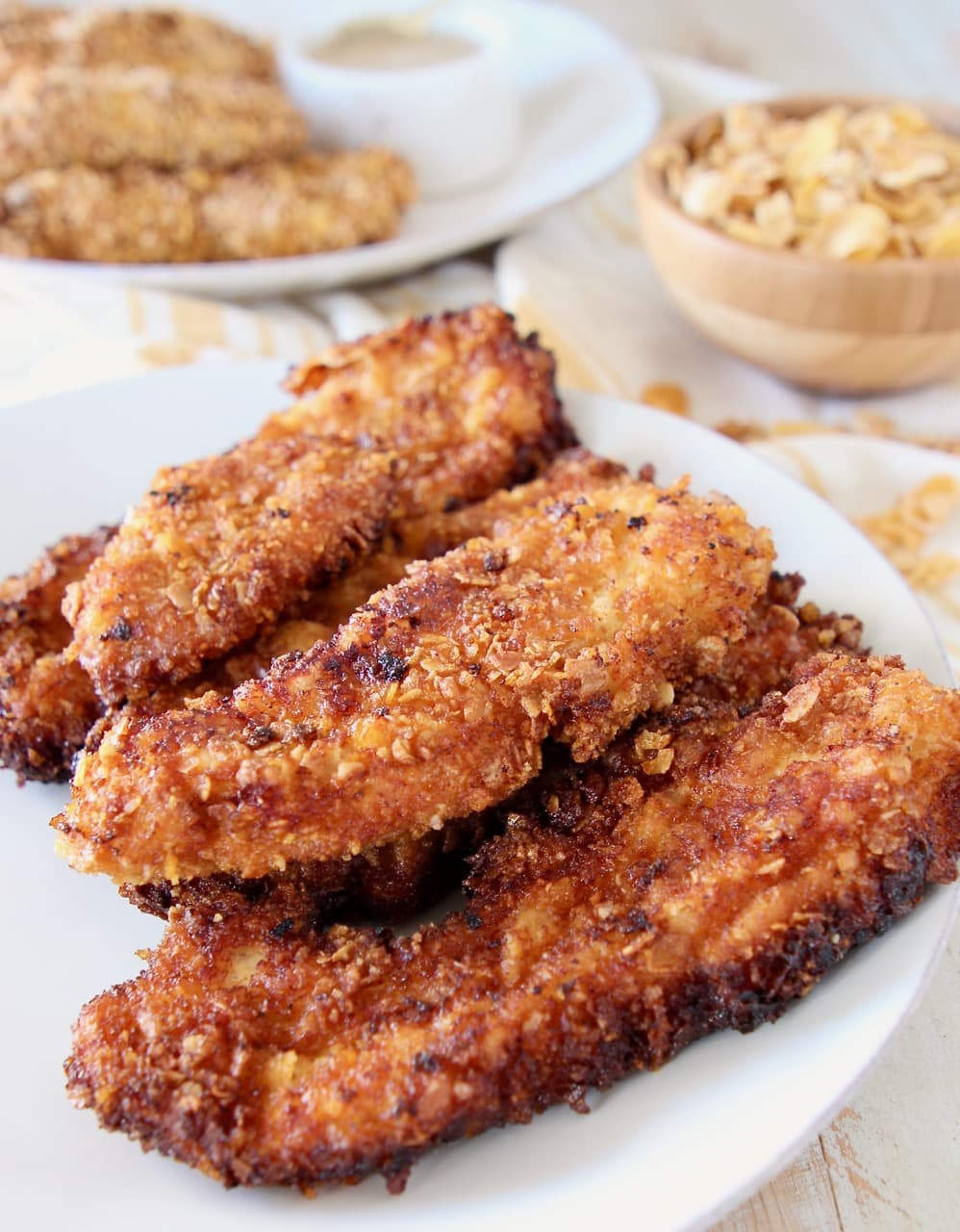 Fried chicken strips on plate with baked chicken strips on plate behind it with bowl of cereal