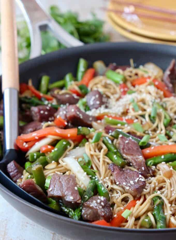 beef stir fry with noodles in skillet with serving spoon