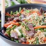 beef stir fry with noodles in skillet with spoon