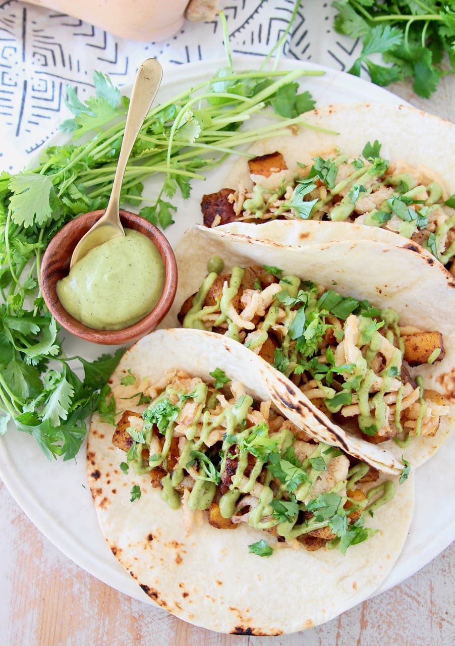 Butternut squash tacos topped with crispy onions, avocado cream sauce and fresh cilantro on plate