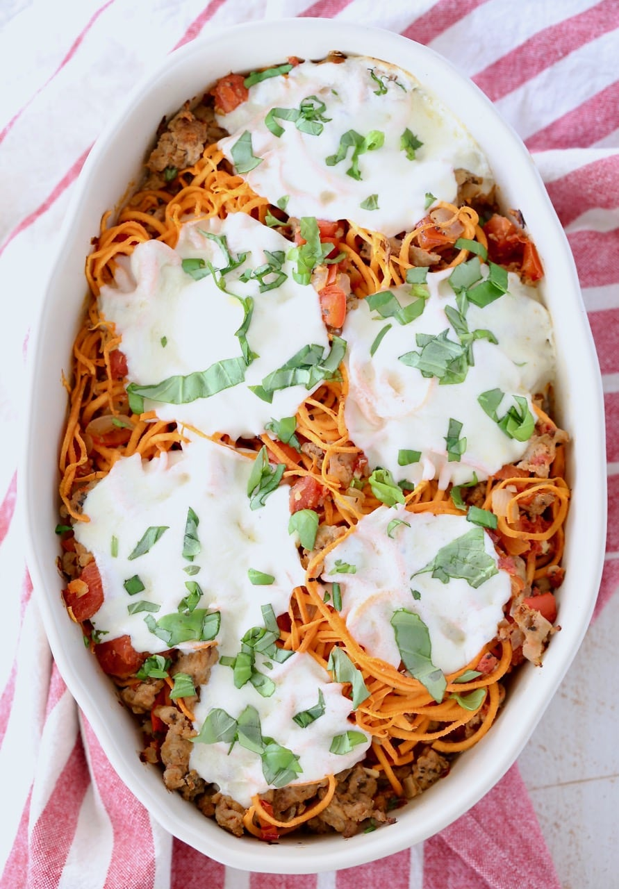 Italian casserole with sweet potato noodles, topped with mozzarella cheese in an oval baking dish
